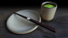 Traditionelle Schale grüner Tee und leere Platte mit Essstäbchen Stockfoto