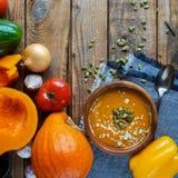 Traditionelle selbst gemachte Kürbissuppe mit seads, Creme und Gemüse auf rustikalem Holztisch Stockfotografie