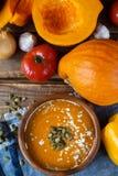 Traditionelle selbst gemachte Kürbissuppe mit seads, Creme und Gemüse auf rustikalem Holztisch Stockfotos