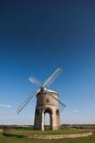 Traditionelle Steinwindmühle unter blauen Himmeln Stockfotografie
