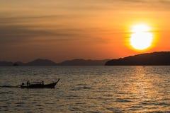 Traditionelle thailändische Boote des Schattenbildes am Sonnenuntergangstrand Lizenzfreies Stockfoto