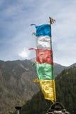Traditionelle tibetanische Gebetsflagge, die gegen blauen Himmel und Berge durchbrennt Stockfotografie