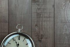 Traditionelle Uhr und hölzerner Hintergrund Viele Kopienraum Stockbilder
