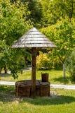 Traditioneller alter hölzerner Brunnen und Eimer Stockfoto