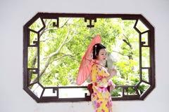 Traditioneller asiatischer japanischer Frauenbrautgriff ein roter Regenschirm, der in einem Garten im Freien lächelt Stockfotos