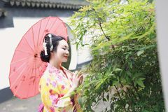 Traditioneller asiatischer japanischer Frauenbrautgriff ein roter Regenschirm, der in einem Garten lächelt Lizenzfreies Stockfoto