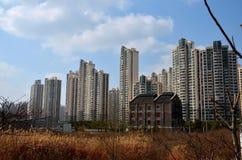 Traditioneller Backsteinbau unter hohen Aufstiegsbetontürmen Shanghai China Stockfotografie