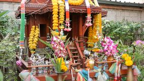Traditioneller buddhistischer Altar im Garten in Thailand, verziert mit Blumen und verschiedenen Symbolfiguren Katze des Rotes stock footage