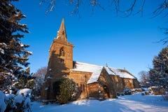 Traditioneller englischer Dorfkirchhof im Schnee Stockbilder