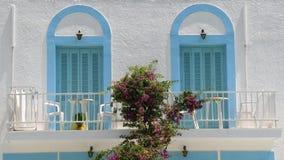 Traditioneller griechischer Balkon mit blauen Tür-Fensterläden und Bouganvilla Stockbild