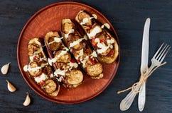 Traditioneller italienischer Teller - grillte die Auberginen, die mit Aufstieg, Tomaten, Knoblauch und Soße auf einer Weinlesepla lizenzfreies stockfoto