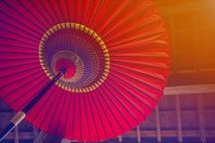Traditioneller japanischer Regenschirm auf einem Holzhauswandhintergrund Stockbild