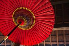 Traditioneller japanischer Regenschirm auf einem Holzhauswandhintergrund Lizenzfreie Stockfotos