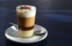 Traditioneller kanarischer Kaffee Barraquito mit den getrennten Schichten Milch kondensiert und Alkohol auf einem dunklen Hinterg lizenzfreies stockfoto
