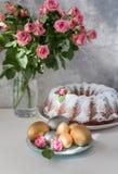 Traditioneller Ostern-Kuchen mit Ostereiern und Blumenstrauß von Rosen auf einem grauen Hintergrund Ostern compisition lizenzfreie stockfotografie