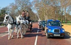Traditioneller Pferdewagen mit britischem Herrn nahe bei einem klassischen London-Fahrerhaus Stockfotos
