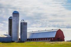 Traditioneller roter Bauernhof und Silos Stockbild