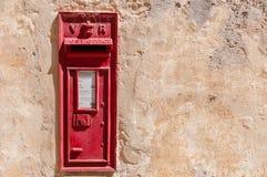 Traditioneller roter Postbox stellte in eine Wand ein Stockbilder
