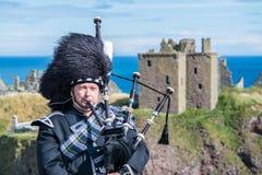 Traditioneller schottischer Dudelsackspieler in der vollen Kleiderordnung an Dunnottar-Schloss Lizenzfreies Stockbild