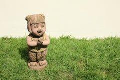 Traditioneller siamesischer Mädchenstatuegruß auf Grasfeld Stockfotografie