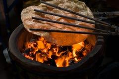 Traditioneller thailändischer Reismehlsnack, der über Feuer und heißen Kohlen kocht Lizenzfreie Stockfotografie