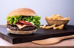 Traditioneller würziger Rindfleischburger mit Salat und Tomate Stockfotografie
