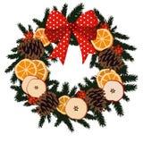 Traditioneller Weihnachtskranz mit Trockenfrüchten - Orange, Apfelscheiben, Kiefernkegel, Beeren auf Immergrün und Band, Dekoratio Lizenzfreies Stockfoto