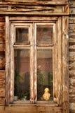 Traditionelles altes russisches Fenster mit Blumen und Statue Lizenzfreies Stockfoto