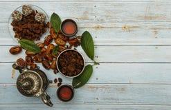 Traditionelles Arabisch, t?rkischer Ramadan-Tee mit trockenen Daten und Rosinen auf einer h?lzernen wei?en Tabelle Eine Tasse Tee stockfoto