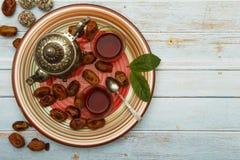 Traditionelles Arabisch, t?rkischer Ramadan-Tee mit trockenen Daten und Rosinen auf einer h?lzernen wei?en Tabelle Eine Tasse Tee lizenzfreie stockbilder