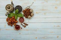 Traditionelles Arabisch, t?rkischer Ramadan-Tee mit trockenen Daten und Rosinen auf einer h?lzernen wei?en Tabelle Eine Tasse Tee lizenzfreies stockfoto