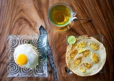 Traditionelles asiatisches Frühstück, Reis mit Ei, Pfannkuchen mit Ananas und Tee auf Holztisch Stockbild