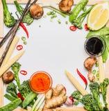 Traditionelles asiatisches Gemüse, das Bestandteile mit Sojasoße und Essstäbchen kocht Stockfotos