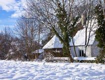 Traditionelles bayerisches Haus mit dem Auferlegen des schräg gelegenen Dachs herein bedeckt durch Schnee stockfotografie