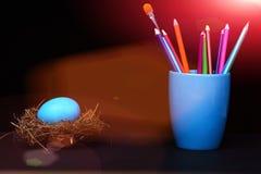 Traditionelles blaues Ei im Nest und Becher mit Bleistiften und Bürste Lizenzfreie Stockbilder