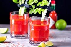 Traditionelles Bloody- Marycocktail mit Selleriestock, Kalk und rosa Salz Lizenzfreie Stockbilder
