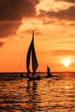Traditionelles Boot im Schattenbild gegen eine untergehende Sonne Lizenzfreie Stockfotos