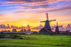 Traditionelles Dorf mit niederländischen Windmühlen und Fluss bei Sonnenuntergang, Holland, die Niederlande Stockbild