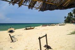 Traditionelles Fischerboot angeschwemmt auf verlassenem sandigem Strand unter hellem sonnigem Tag Stockbild