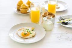 Traditionelles Frühstück mit Spiegelei, Jogurt, selbst gemachten Muffins, Zitrusfruchtklumpen und Orangensaft Stockfotos