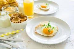 Traditionelles Frühstück mit Spiegelei, Jogurt, selbst gemachten Muffins, Zitrusfruchtklumpen und Orangensaft Stockfoto