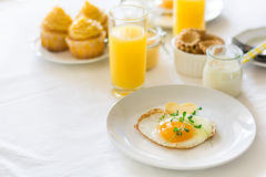 Traditionelles Frühstück mit Spiegelei, Jogurt, selbst gemachten Muffins, Zitrusfruchtklumpen und Orangensaft Stockfotografie
