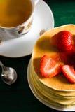 Traditionelles Frühstück: Pfannkuchen mit dem Sirup und Erdbeere, grün stockfoto