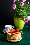 Traditionelles Frühstück: Pfannkuchen mit dem Sirup und Erdbeere, grün stockbild