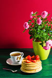 Traditionelles Frühstück: Pfannkuchen mit dem Sirup und Erdbeere, grün lizenzfreie stockfotografie
