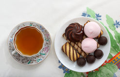 Traditionelles Frühstückskonzept mit bunter Tasse Tee, Bonbons und Kekse auf weißer Tischdecke mit buntem Druck Stockfotografie