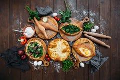 Traditionelles georgisches adjara khachapuri und Kolkh-khachapuri auf dem Tisch Selbst gemachtes Backen Beschneidungspfad eingesc Lizenzfreie Stockfotografie
