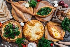 Traditionelles georgisches adjara khachapuri und Kolkh-khachapuri auf dem Tisch Selbst gemachtes Backen Beschneidungspfad eingesc Lizenzfreie Stockfotos