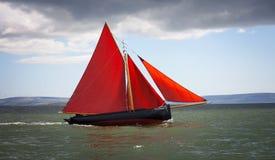 Traditionelles hölzernes Boot mit rotem Segel Stockfotografie