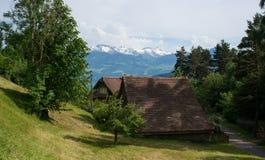 Traditionelles hölzernes Haus vor den Schweizer Bergen Stockbilder